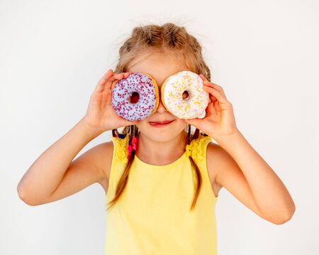 happy cute blond girl holding two donuts on her eyes