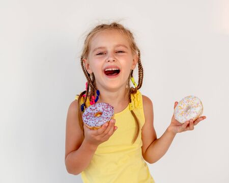 cute little girl holding two donuts