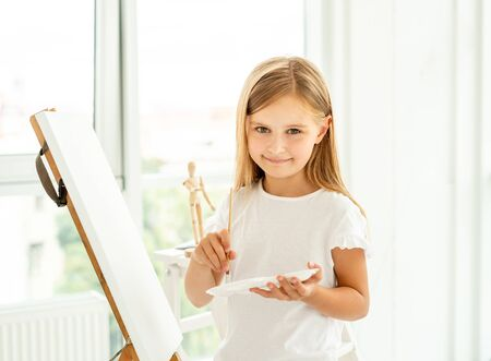 Cute little girl paints on canvas
