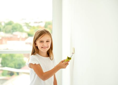 Little cute girl paints a wall with paint roller