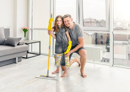 Little girl with father cleaning the floor 免版税图像