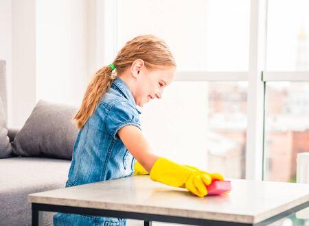 Bambina che pulisce il tavolo in legno Archivio Fotografico