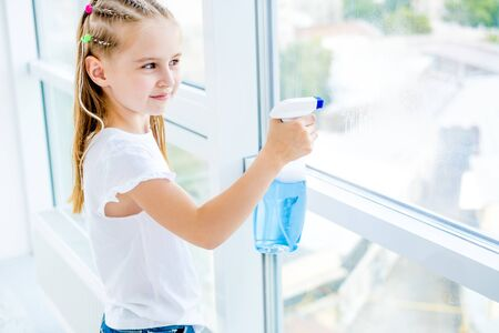 Kleines Mädchen, das das Fenster putzt Standard-Bild