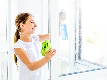 Teen girl cleaning window with spray