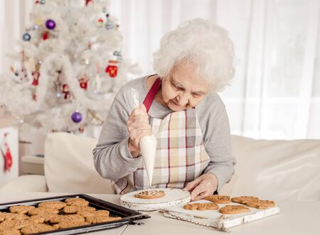 Elder woman soaking cream on Christmas cookies 写真素材