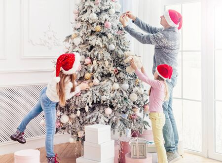 Father and daughters decorating christmas tree 写真素材