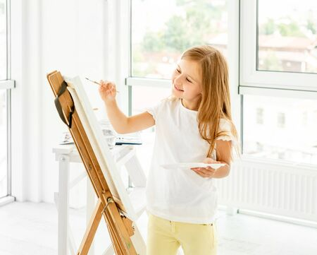 Kid girl drawing with oil paint and palette