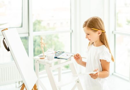 Kid girl painting different pictures on easel