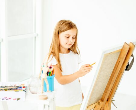 girl makes pencil sketch on canvas