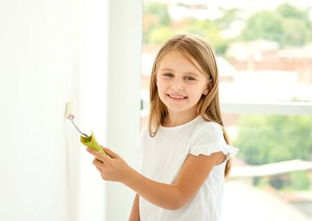 little cute girl paints a wall with paint roller Zdjęcie Seryjne