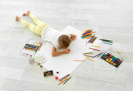 Little girl drawing on paper, lying on the floor