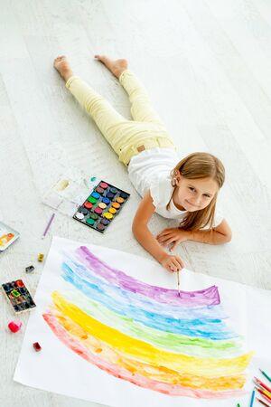 little girl draws lying on the floorlittle cheerful girl draws lying on the floor 免版税图像