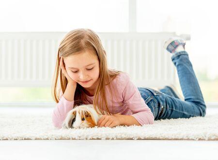 Girl holding guinea pig on the floor