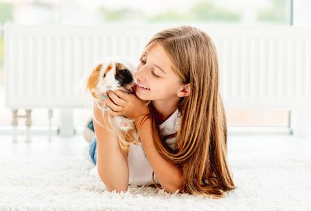 Young teen girl holding guinea pig on the floor