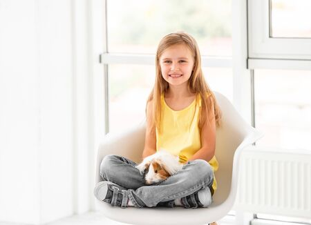 Smiling kid girl holding cute guinea pig