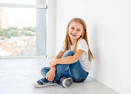 Smiling little girl sitting on the floor