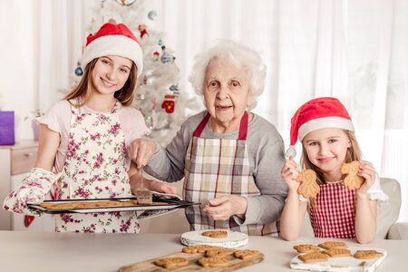 Grandmother with granddaughters baking cookies Stock Photo