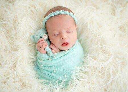 Sleeping newborn in blue headband Archivio Fotografico - 129218180