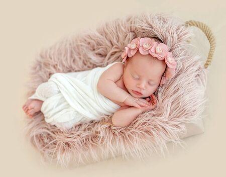 Cute newborn girl sleeping in child basket
