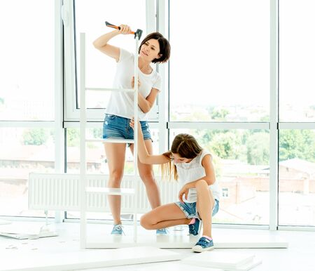 Mother and daughter together working with furniture