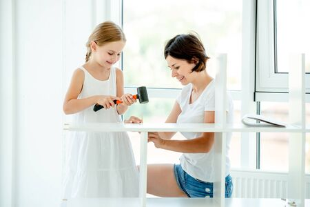 Mother teaching kid girl how to work with instruments