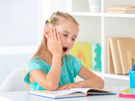 Girl yawning in front of open book