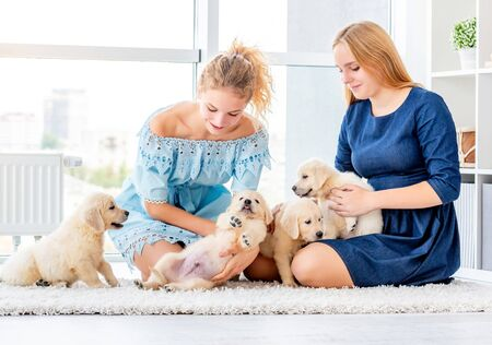 Girls play with retriever puppies