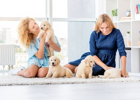Girls playing with retriever puppies