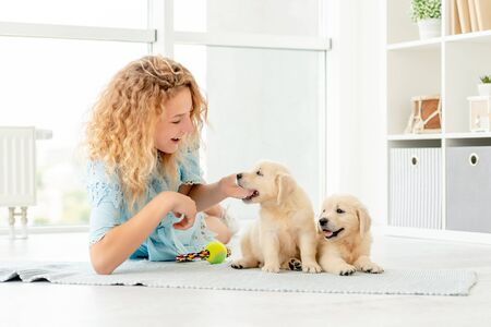 Girl relaxing with retriever puppies