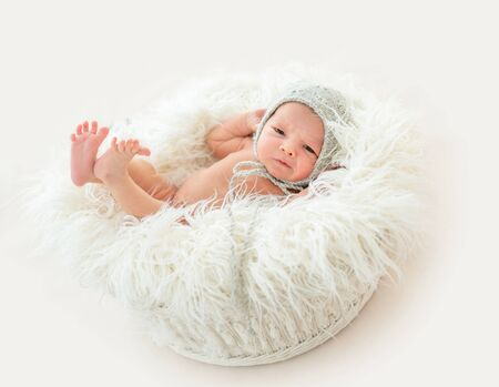 Cute newborn boy lying in a basket Archivio Fotografico - 130854794