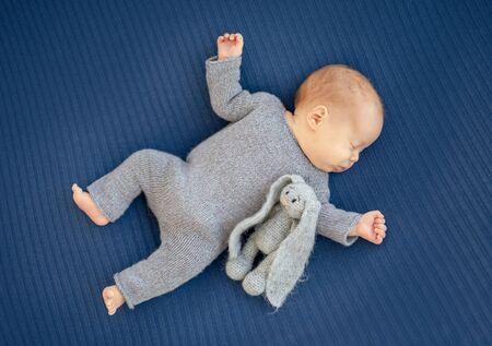 Newborn sleeping on back near toy
