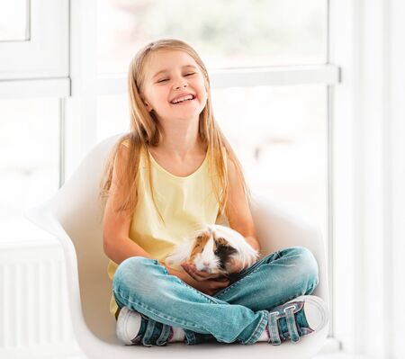 Smiling kid girl holding cute guinea pig
