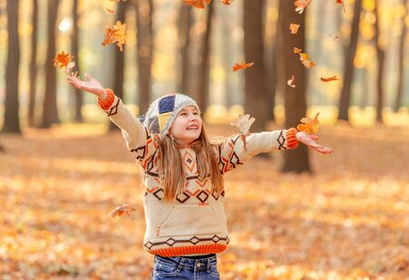 Little girl throwing up leaves