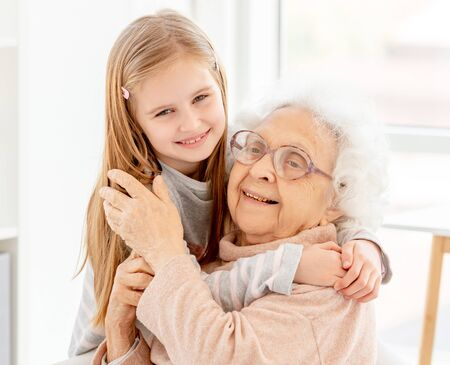Little girl embracing grandmother Stock Photo