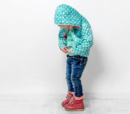 little girl fastening her blue dotted jacket Stock Photo