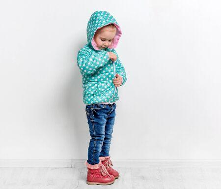 little girl fastening her blue jacket Stock Photo