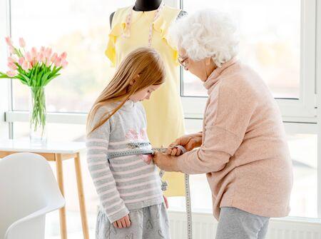 Senior lady measuring little model Imagens
