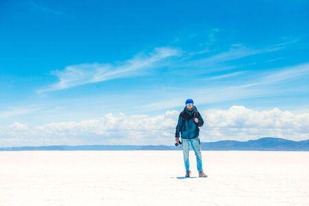 Tourist with equipment and camera walking in sunshine Salar de Uyuni 写真素材