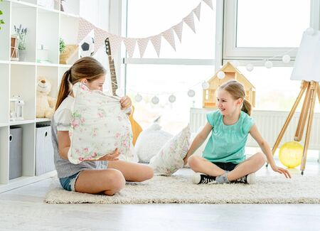 Smiling girls fighting with pillows Banco de Imagens