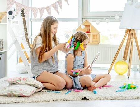 Sister making hairstyle to little girl Banco de Imagens