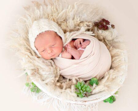 Charming awake newborn lying in cradle