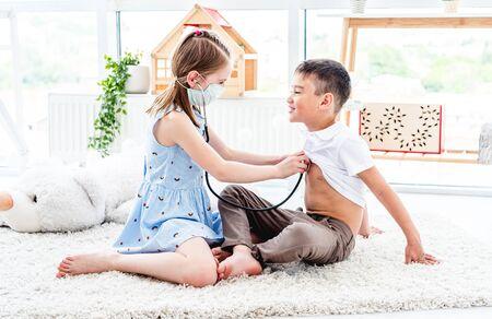 Happy kids playing doctor in light room