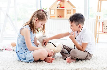 Children playing doctor with teddy bear