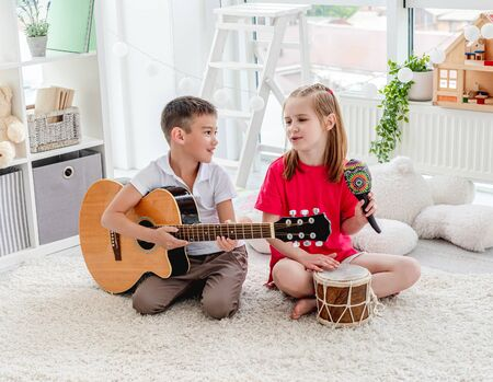 Smiling kids playing on drum and guitar 免版税图像