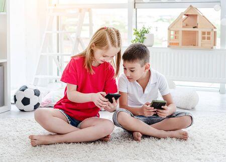 Smiling children looking at smartphone 免版税图像