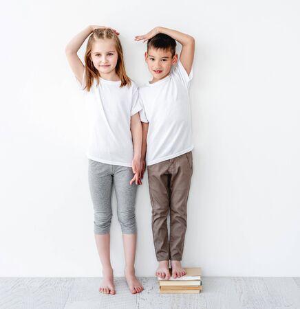 Little boy standing on books near sister