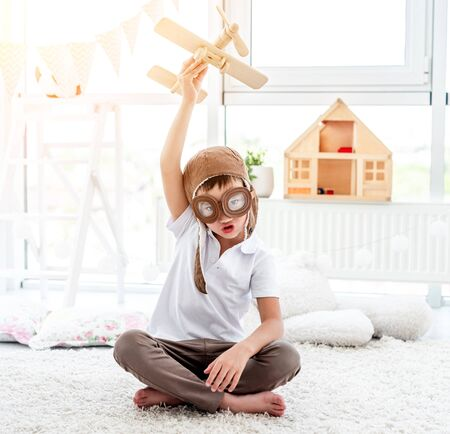Happy little boy playing with plane
