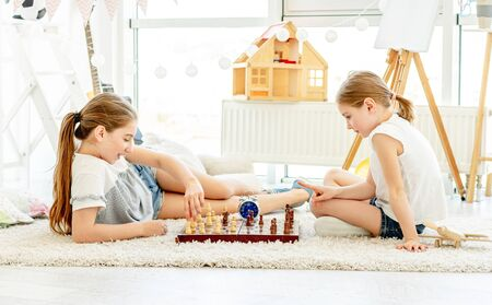 Beautiful sisters playing chess on floor 免版税图像