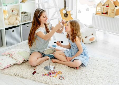 Cheerful girls kids playing with makeup Banco de Imagens