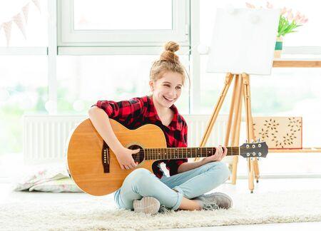 Smiling teenage girl playing guitar